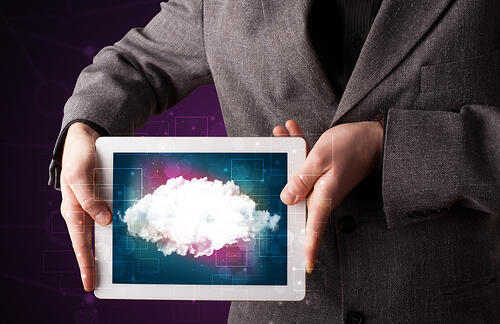 Casual businessman holding tablet with cloud icon and purple background