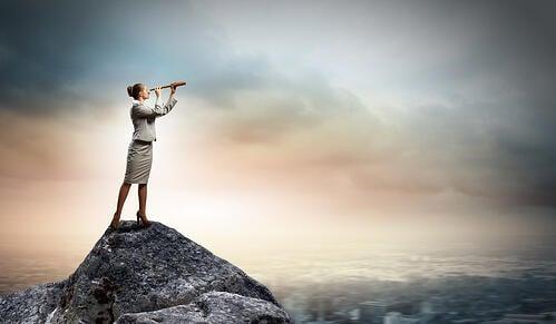 Image of businesswoman looking in telescope standing atop of rock