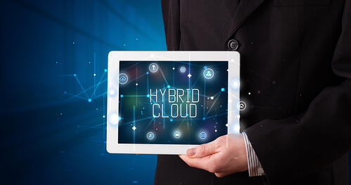 Young business person working on tablet and shows the digital sign HYBRID CLOUD