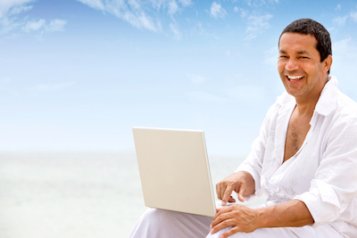 beach man happy and smiling on a laptop computer
